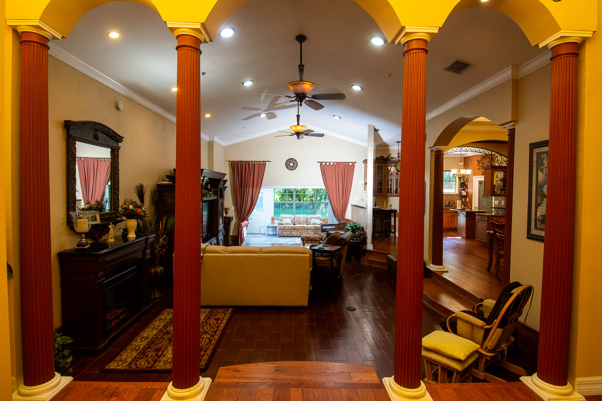 Entryway view of living room with Grecian columns with fireplace, vaulted ceiling and a view of the sun room,back yard and kitchen