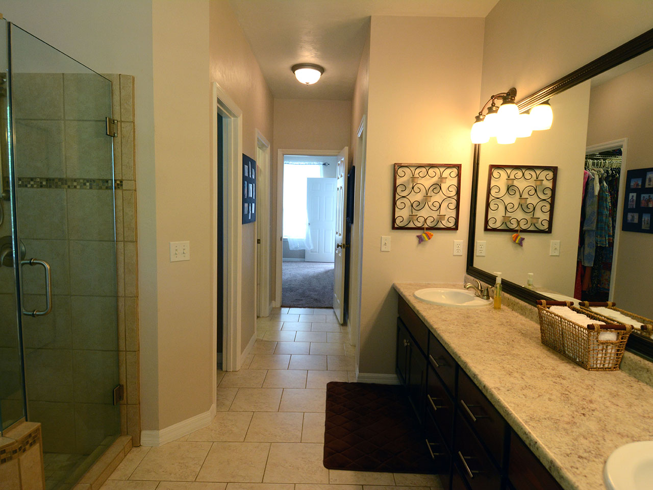 Bathroom with glass shower enclosure, double sink vanity, tile floor and a separated water closet and closet