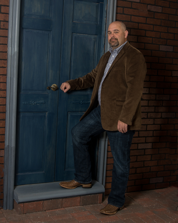 Country attorney standing outside a brick building with a blue door