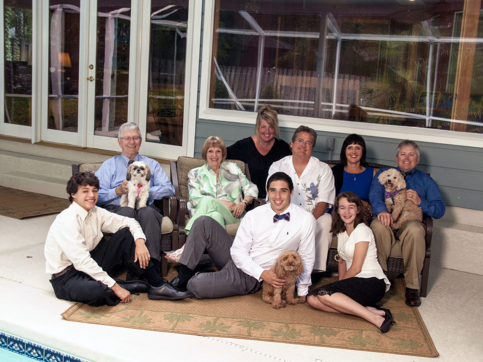 Large family portrait by pool with brothers sisters aunts uncles and grandparents