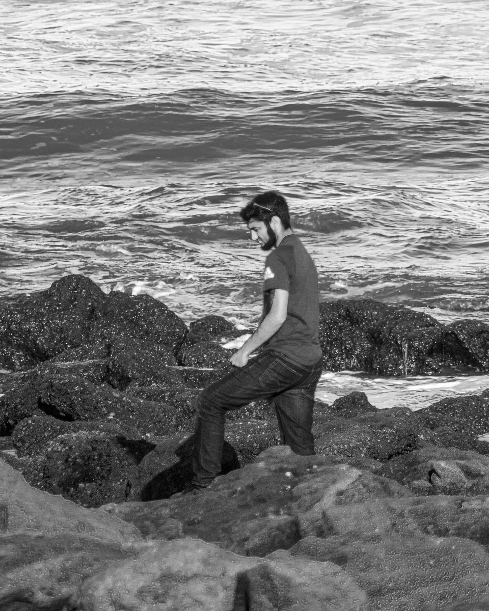 Man at the beach standing in the rocks with waves behind him portrait black and white