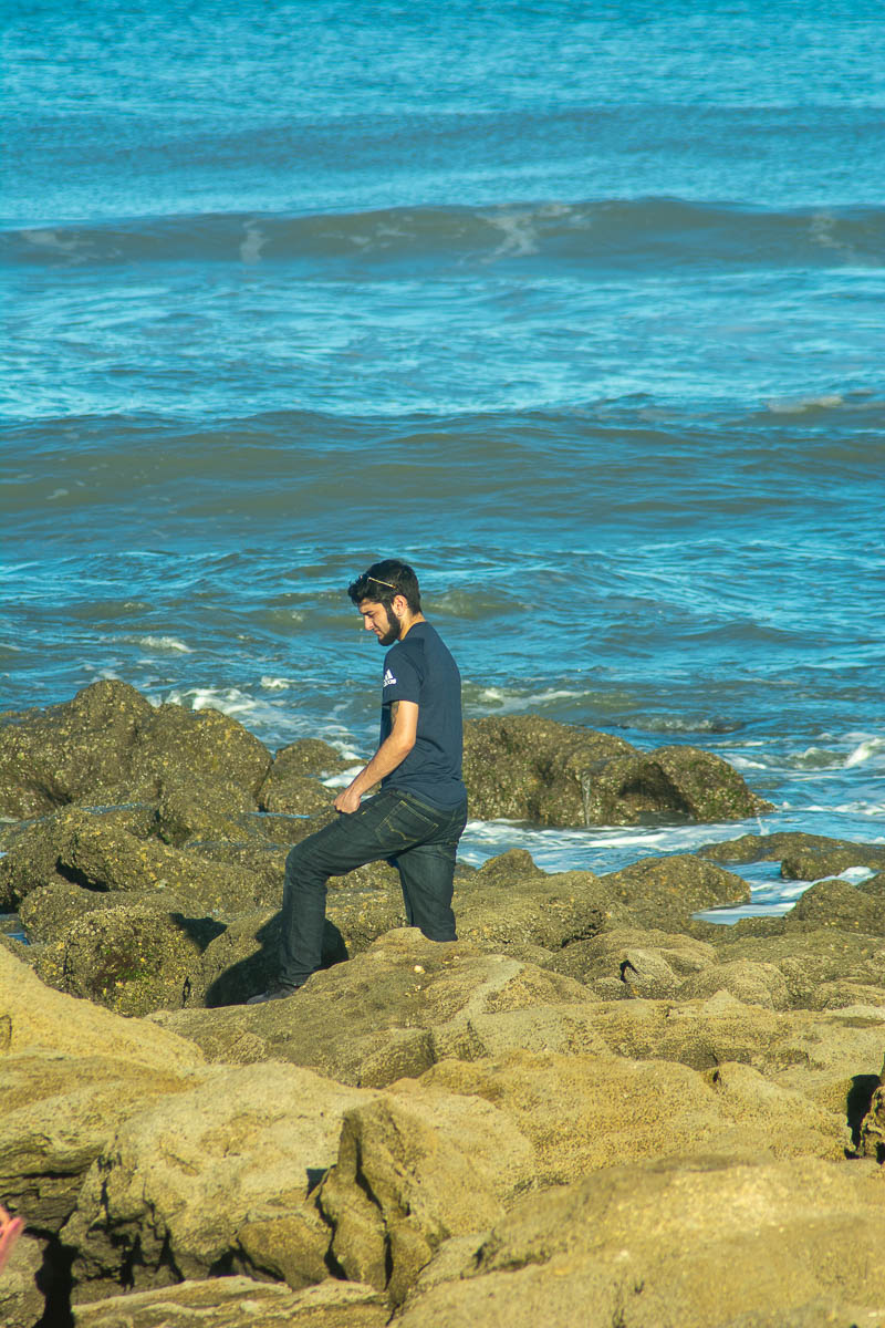 Young man at the beach standing in the rocks with waves behind color