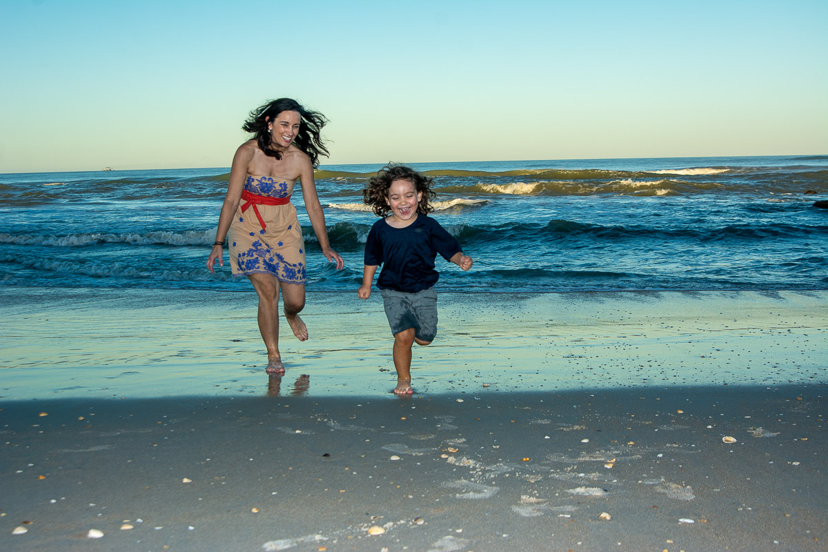 Mother with hair blowing in the wind as she chases her young son at the beach