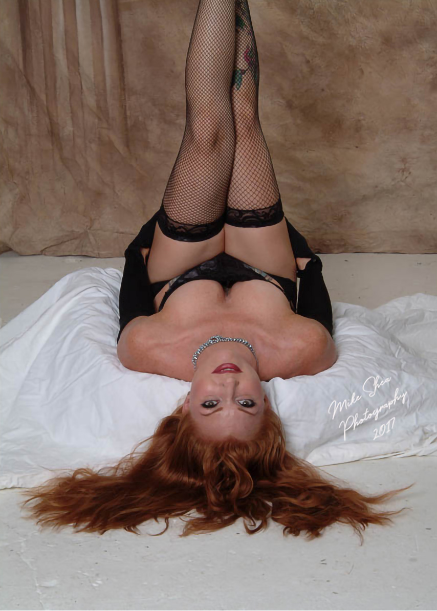 Beautiful Redhead laying on floor in lingerie with hair spread out