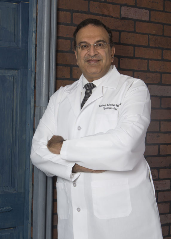 Eye Surgeon, white coat, glasses leaning against a doorway