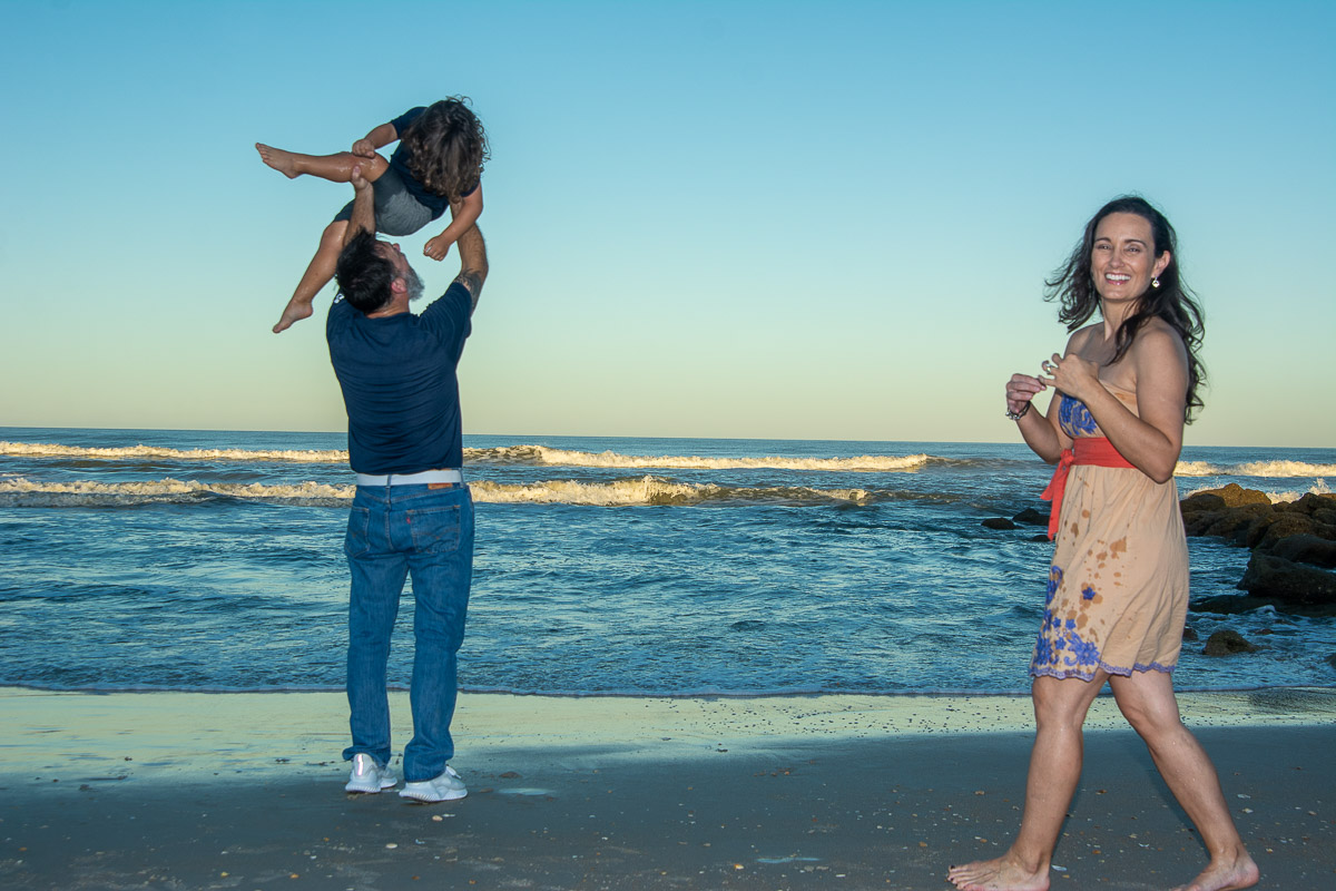 Dad swinging son in air at beach sunset with mother watching portrait