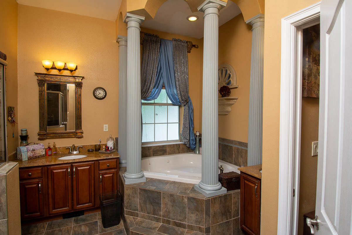 Master bath, vaulted ceiling en suite with luxurious tile, columned garden tub and separate water closet