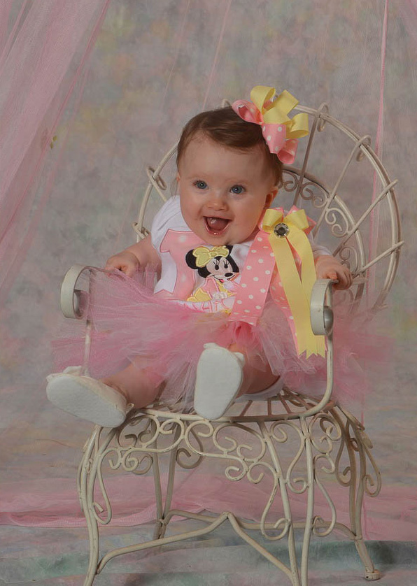 Happy baby girl at first birthday portrait pink fluffy dress and ribbon in hair
