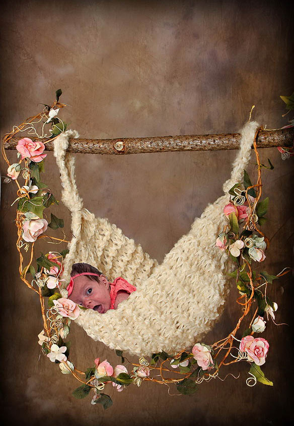 Baby girl in a crocheter hammock with roses