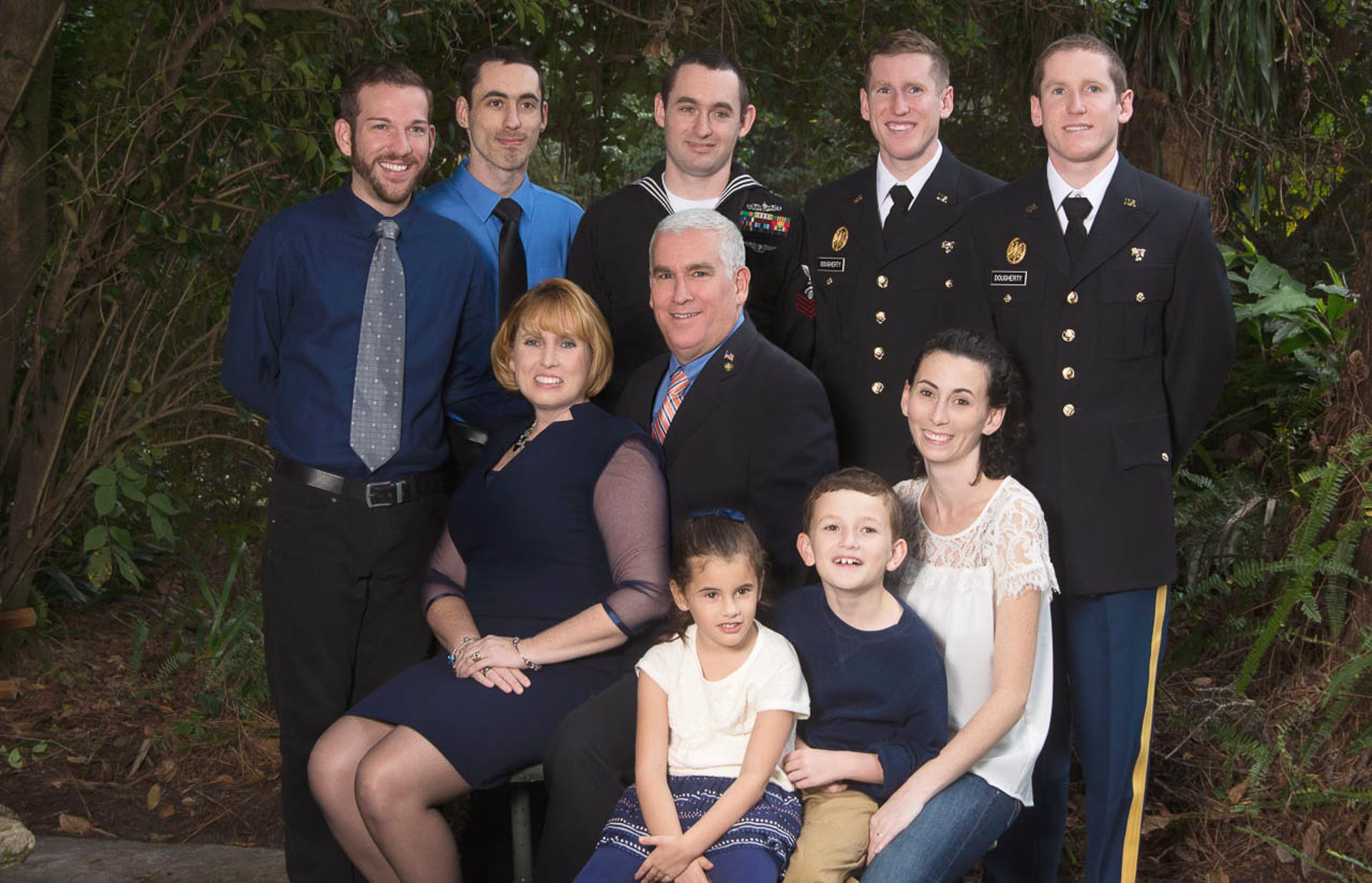 Father, mother and armed forces children in uniform with grandchildren outside