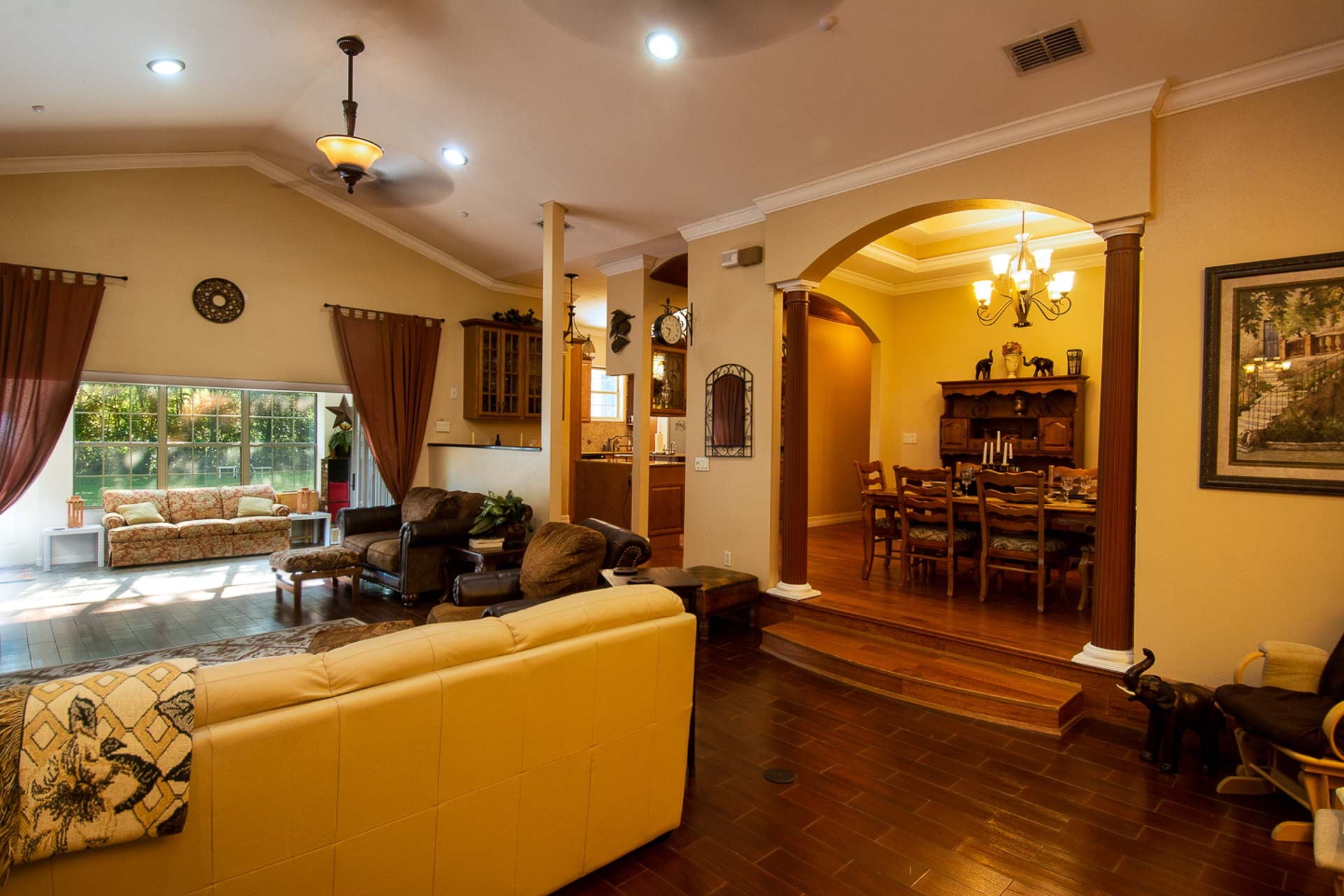 This large living room with vaulted ceiling, recessed lighting, and large columned archway to formal dining room