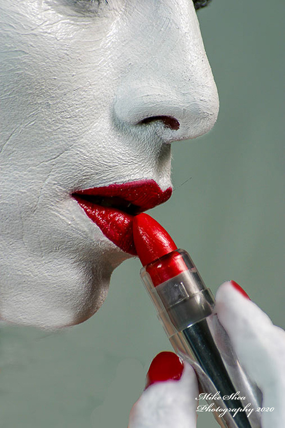 Art image of a woman as a living canvas with red lipstick and a silver lipstick tube