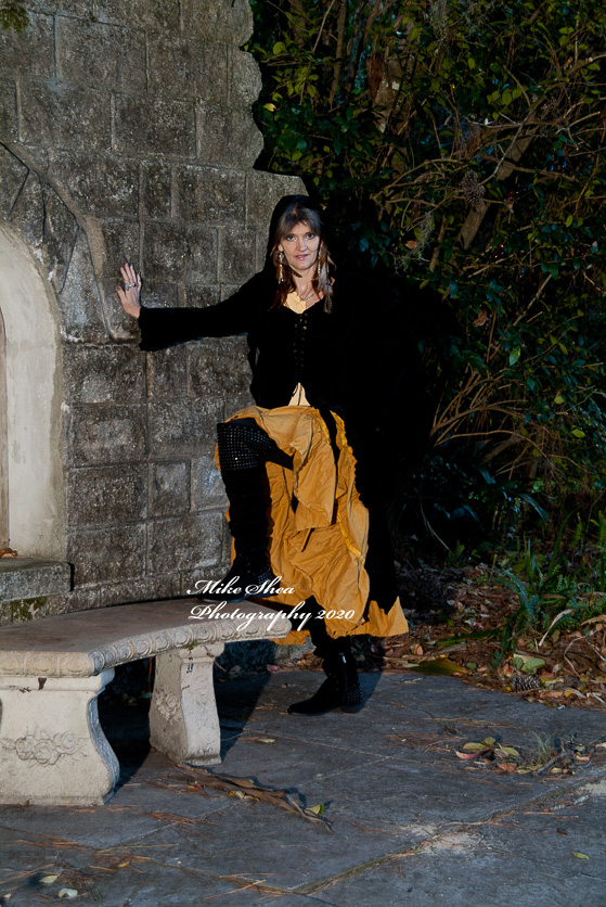 Young Woman in a Gypsy garb by a castle wall